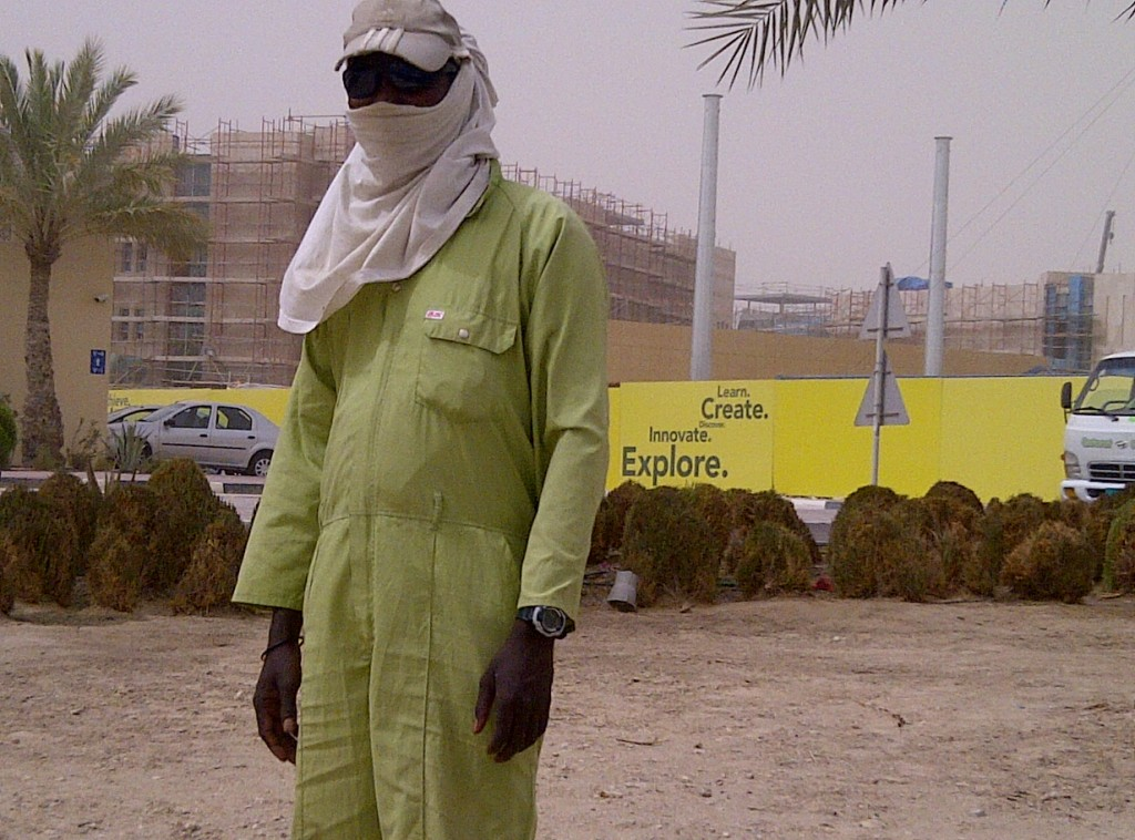 A laborer working as a gardner on a dusty day in Doha.
